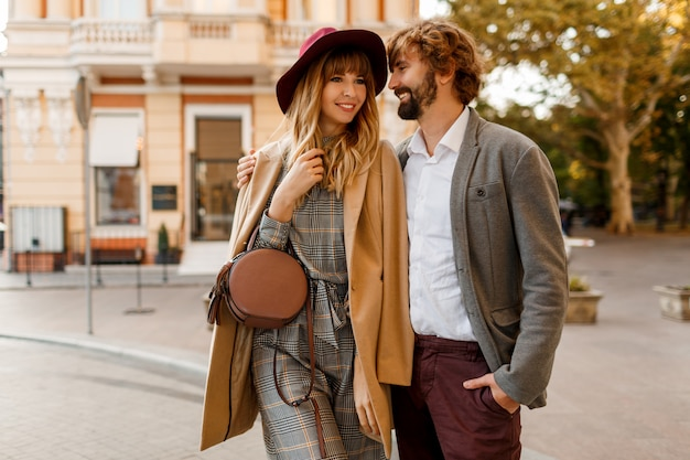Close up portrait of amazing stylish couple in love spending romantic holidays in european city. pretty blond woman in hat and casual dress smiling and looking on her handsome man with beard.