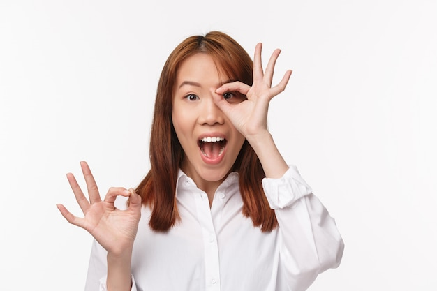 Close-up portrait amused and excited asian woman in white shirt, look amazed glancing through okay gesture with fascinated expression, found something really good, recommend buy, white wall
