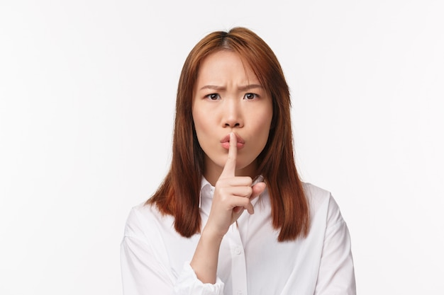クローズアップの肖像画の怒っているアジアの女性の大声で人を叱る、カメラプレスの人差し指を唇に押しつけ、静かにするか静かにしてください、