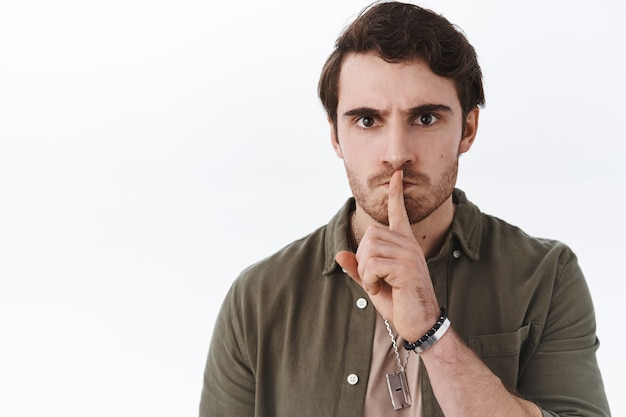 Close-up portrait angry bossy handsome guy tell keep quiet, asking silence, shushing with finger pressed to lip
