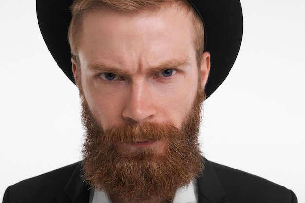 Chiuda sul ritratto del ragazzo brutale arrabbiato con la barba lunga spessa che posa in vestito elegante e cappello accigliato, avendo un'espressione facciale dispiaciuta furiosa, esprimendo emozioni negative ostili