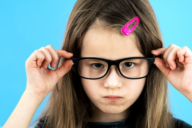 Close up portrait of angry displeased child school girl wearing looking glasses isolated on blue background.