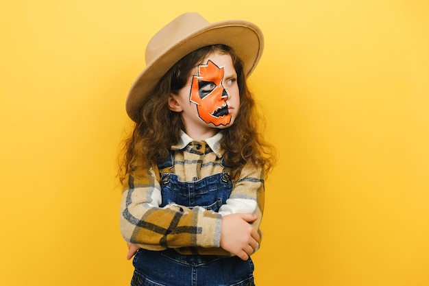 Close up portrait of angry sad little girl child with halloween makeup mask, wears brown hat and shirt, crossed arms looking to side, isolated over yellow studio background wall with copy space