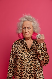 Close up portrait of angry wrinkled fashionable granny