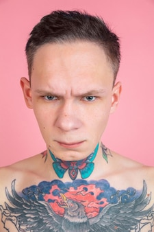 Close up portrait of angry young man with tattoos on pink wall