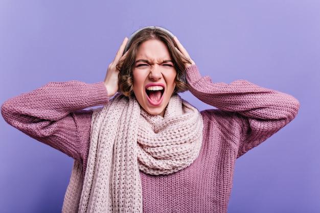 Ritratto del primo piano di giovane donna arrabbiata in sciarpa lavorata a maglia. foto dell'interno della ragazza emotiva dai capelli corti in posa con l'espressione del viso sconvolta.