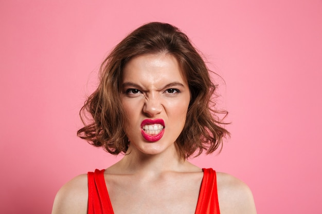 Close-up portrait of angry young woman with red lips
