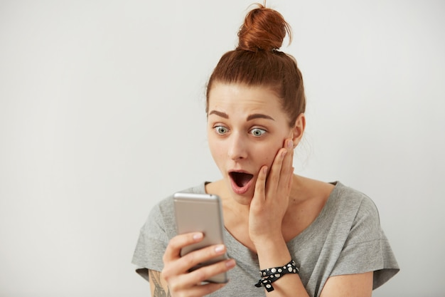 Close up ritratto ansioso o scioccato giovane donna freelance guardando il telefono vedendo cattive notizie
