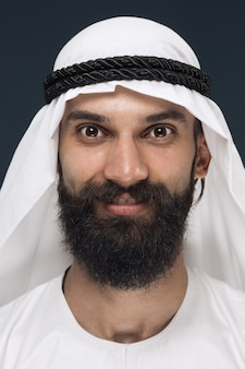 Chiuda sul ritratto dello sceicco saudita arabo. giovane modello maschio in piedi e sorridente, sembra felice.