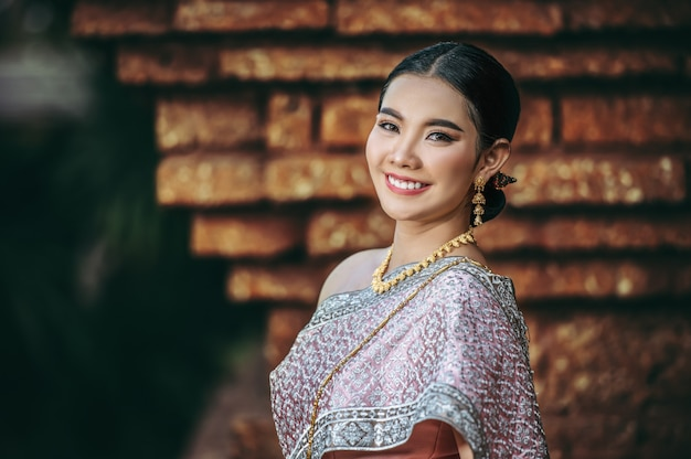 Close up, portrait asian charming woman wearing beautiful typical thai dress in ancient temple or famous place with gracefully pose