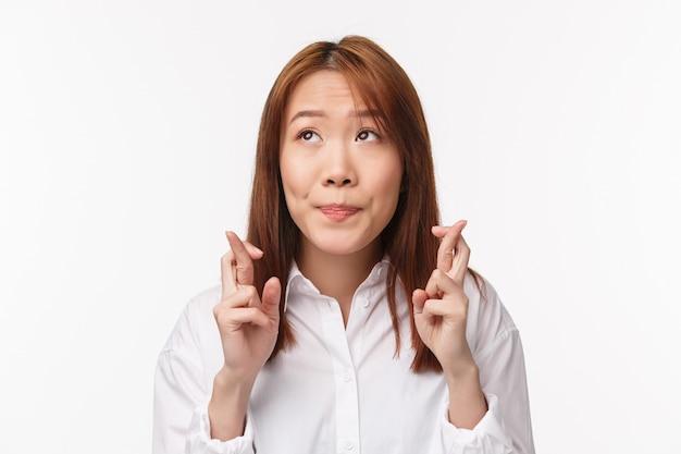Крупным планом портрет азиатских обнадеживающих и робких женщина смотрит мечтательно и вдумчиво, глупо улыбаясь, скрестив пальцы удачи как молиться, мечта мечты сбываются, стоя на белой стене