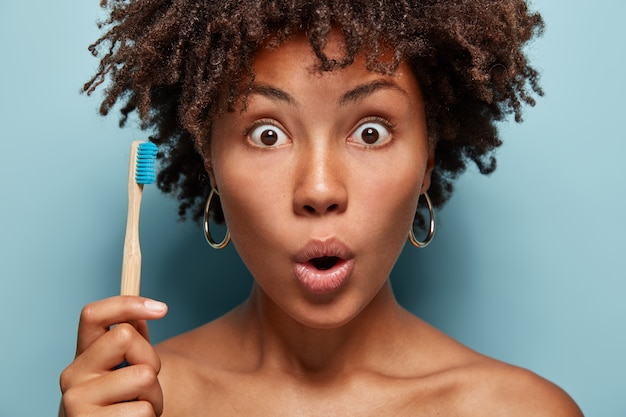 Close up portrait of astonished black woman stares with bugged eyes, opens mouth, holds wooden brush, prepares for cleaning teeth, surprised with effect of toothpaste, has healthy dark skin.