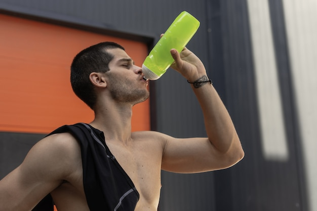 Close-up portrait athletic sportsman drinking watter