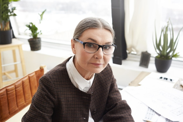 Close up portrait of attractive 60 year old caucasian woman designer with gray hair wearing rectangular eyeglasses doing paperwork in her light workspace, looking with serious expression