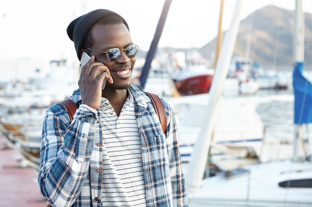 Close up portrait of attractive and charismatic dark-skinned guy in stylish cap and fashionable oval shaped mirror glasses carrying backpack on his shoulders, smiling while talking on cell phone