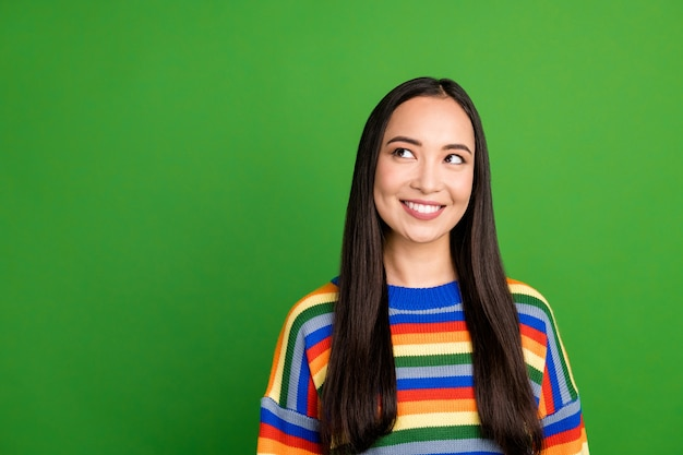Close-up portrait of attractive curious cheerful girl wearing striped pullover thinking copy space isolated over bright green color background