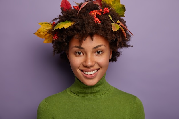 Close up portrait of attractive curly woman feels pleased, shows white perfect teeth, smiles broadly, has stylish haircut with autumnal leaves, expresses positive emotions