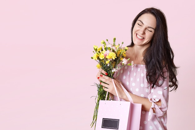 Close up portrait of attractive dark haired young woman in dress, enjoys spring coming, likes to get flowers and presents from her hasband, screw eyes hapily. people, presents, celebration concept.