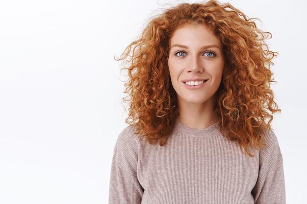 Портрет крупным планом привлекательная, женственная милая рыжая женщина с вьющимися натуральными волосами, в бежевой блузке, улыбающаяся зубастая с восхищенным, восторженным выражением лица, стоящая у белой стены удивленно