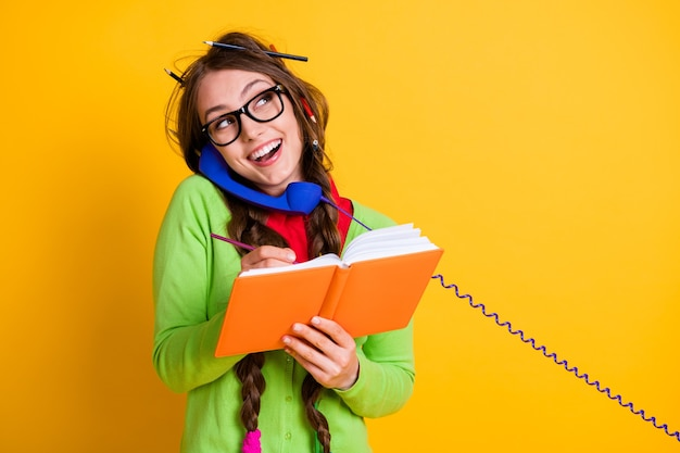 Close-up portrait of attractive funky cheerful girl talking on phone writing home task discussing isolated bright yellow color background