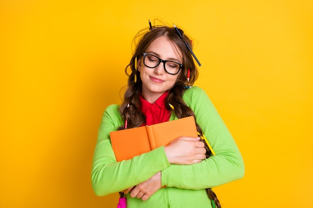 Close-up portrait of attractive funky dreamy cheery teenage girl hugging exercise book literacy isolated over shine yellow color background
