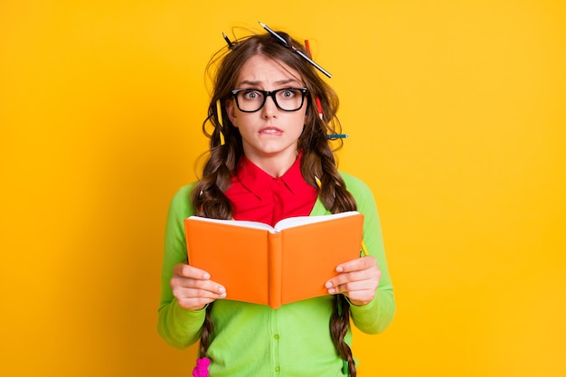 Close-up portrait of attractive funky worried teenage girl reading exercise book biting lip isolated over bright yellow color background