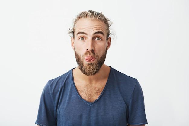 Chiuda sul ritratto del tipo divertente attraente con l'acconciatura alla moda e la barba che mostrano la lingua e che fanno l'espressione sciocca