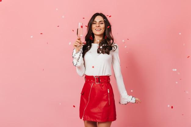 Ritratto del primo piano della ragazza attraente in gonna luminosa e camicetta luminosa in posa con un bicchiere di champagne su sfondo rosa.
