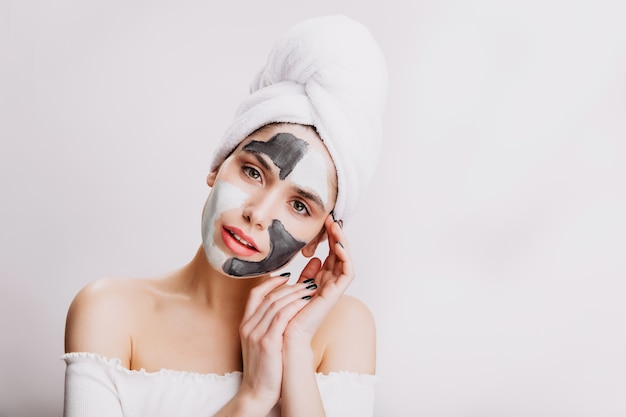 Close-up portrait of attractive girl doing facial mask before bedtime. adult woman posing on white wall.