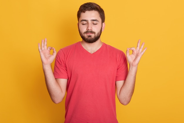 Chiuda sul ritratto dell'uomo attraente che indossa la maglietta casuale rossa che gesturing il segno giusto con gli occhi chiusi