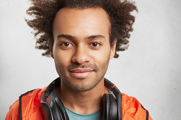 Close up portrait of attractive man with afro hairstyle, stubble, wears orange anorak