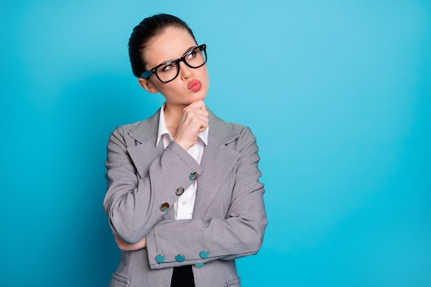 Close-up portrait of attractive pensive lady ceo boss chief thinking pout lips touching chin isolated on bright blue color background