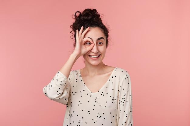 Chiuda sul ritratto della ragazza castana affascinante positiva attraente con i capelli raccolti dell'onda che fa il simbolo okey vicino agli occhi con una mano, in camicetta con pois, isolata