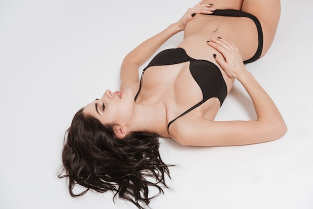 Close up portrait of an attractive seductive woman laying on the floor isolated