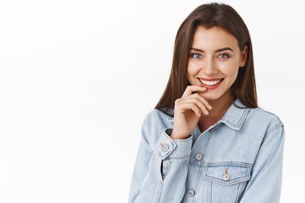 클로즈업 초상화는 사랑스러운 미소를 지닌 매력적인 관능적이고 여성스러운 여성, 만지는 입술, 데님 재킷을 입고 흰색 배경 위에 서서 바람둥이와 유혹을 표현하는 것처럼 코케티시를 웃습니다.