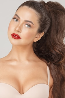 Close up portrait of attractive sexy woman with red lips posing looking at camera. face of beauty fashionable girl in nude bra and luxury makeup isolated at white studio background