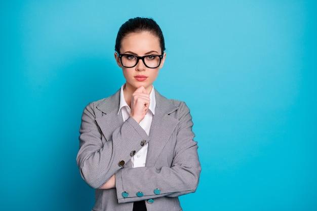 Close-up portrait of attractive smart content businesslady thinking touching chin isolated over bright blue color background
