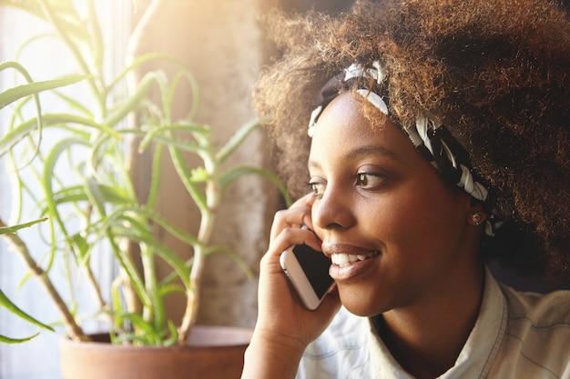 Close up ritratto di attraente ed elegante ragazza dalla carnagione scura con acconciatura afro indossa bandana parlando al cellulare al suo ragazzo che osserva da parte