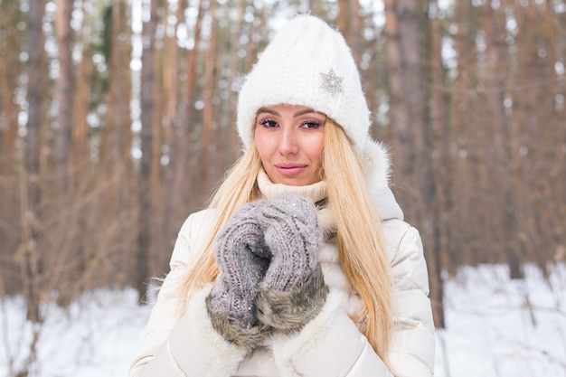 Close up portrait of attractive woman dressed in white hat in winter