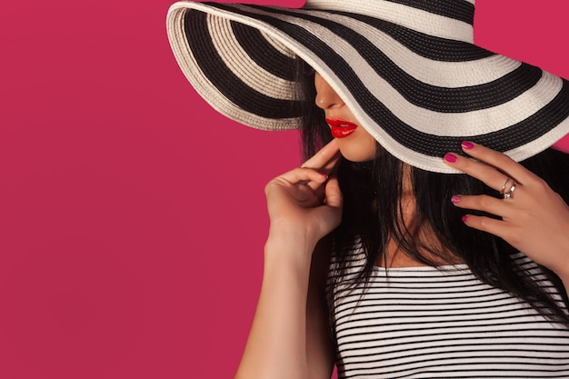 Close-up portrait or attractive woman in stripped sunscreen hat. unrecognizable beautiful woman on pink wall