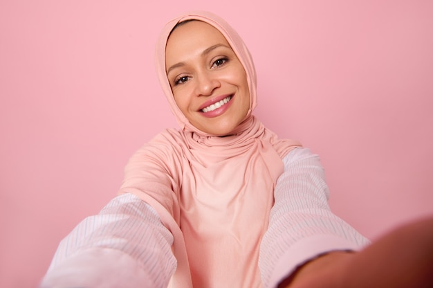 Close-up portrait of an attractive woman wearing traditional religious islamic outfit, pink hijab, holding smartphone in outstretched arms and smiles with toothy smile making a selfie, self-portrait
