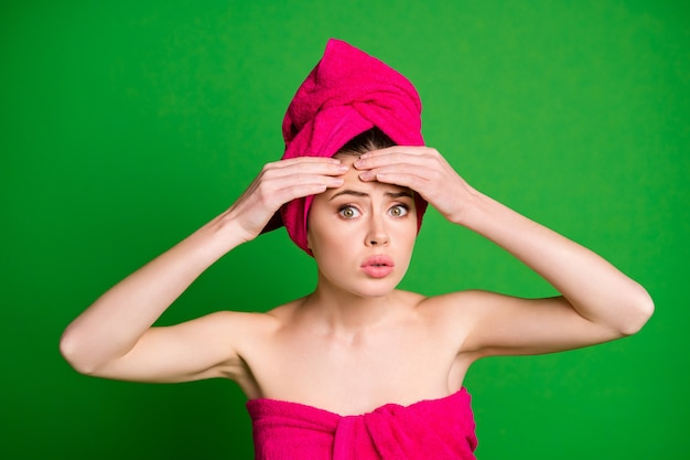 Close-up portrait of attractive worried lady wearing turban touching forehead pustule isolated on bright green color background