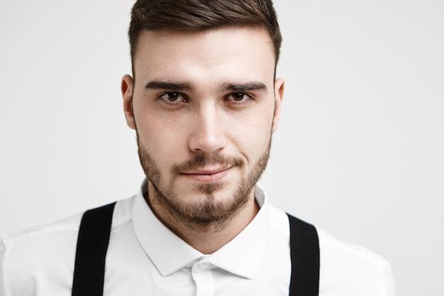 Chiuda sul ritratto di giovane uomo castana attraente con l'acconciatura alla moda e la barba tagliata che posa allo studio bianco che indossa camicia formale e bretelle, fiducioso sul prossimo colloquio di lavoro