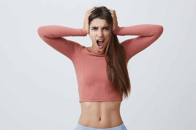 Close up portrait of attractive young expressive caucasian woman with dark long hair in pink top and blue shorts squeezing head with hands with angry expression,screaming loudly.