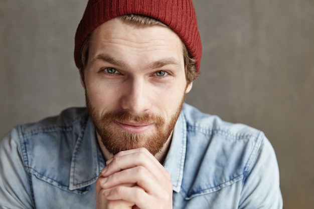 Close up portrait of attractive young male with thick beard and charming blue eyes wearing stylish clothing, looking with flirty smile, keeping hands on his chin. people and lifestyle