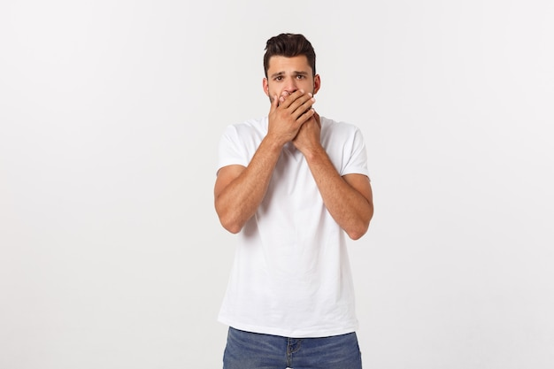 Close up portrait of attractive young man closing his mouth with fingers. worried gesture, can't say anything.