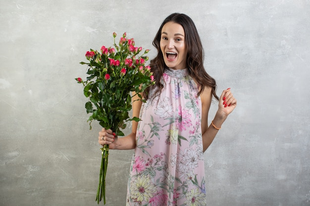Close-up portrait of attractive young woman in summer dress holding bouquet of roses