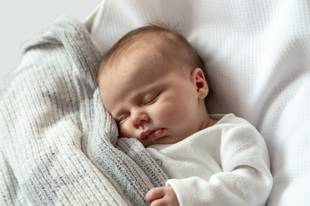 A close-up portrait of a baby girl who sleeps in a cradle or crib