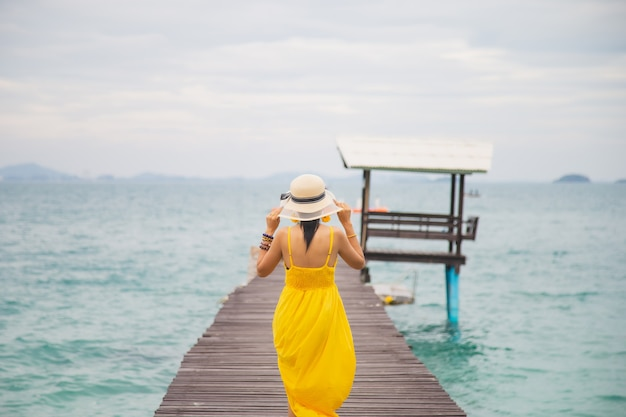 Close up portrait back young asian woman in a yellow dress touching a hat on her head walking on a wooden bridge on the beach with a sky background