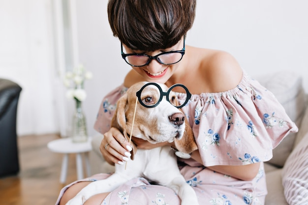 Close-up portrait of beagle dog with big sad eyes and cheerful girl with short haircut holding glasses
